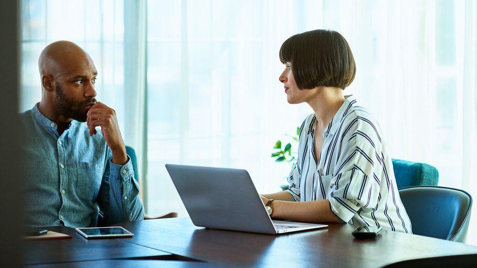 An employee talks to a female boss