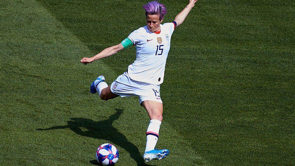 Megan Rapinoe kicking a ball