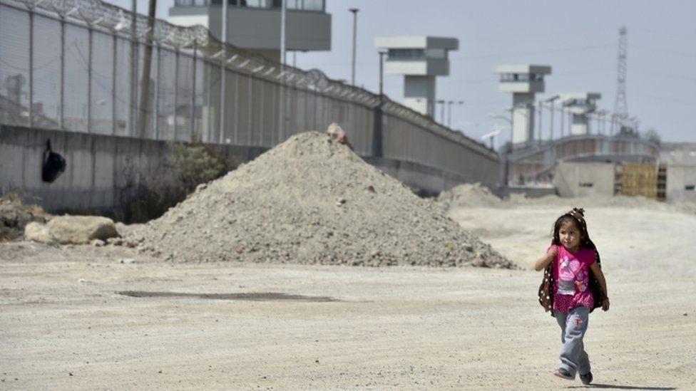 "A girl walks along the perimeter wall of the El Altiplano prison, where Mexican drug lord Joaquin ""El Chapo"" Guzman is being held, on February 24, 2016 in Almoloya de Juarez, Mexico. AFP"