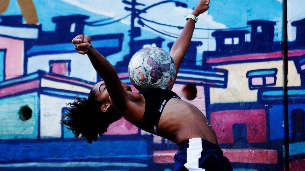 Thamires在胸前垫了一个球,双臂伸展平衡,后仰向后倾斜