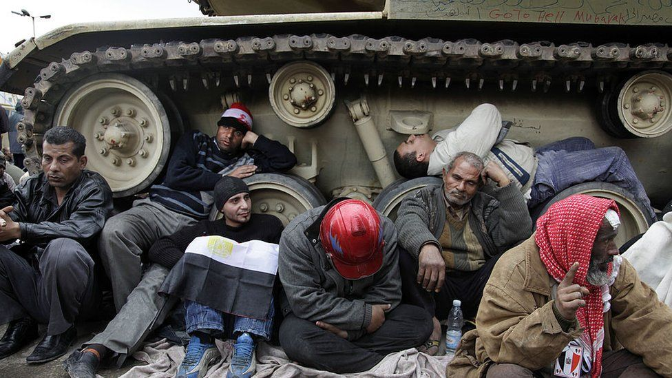 Protesters huddle beside the tracks of a tank in Cairo (06/02/11)