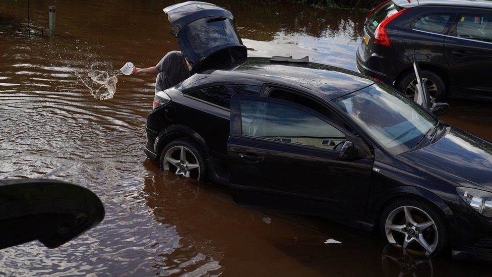 Resident in Rothbury in Northumberland bails water from their vehicle after the River Coquet burst its banks