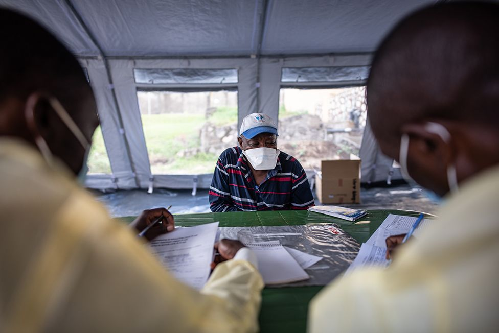 Nicolas gives his details to nurses in the vaccine tent