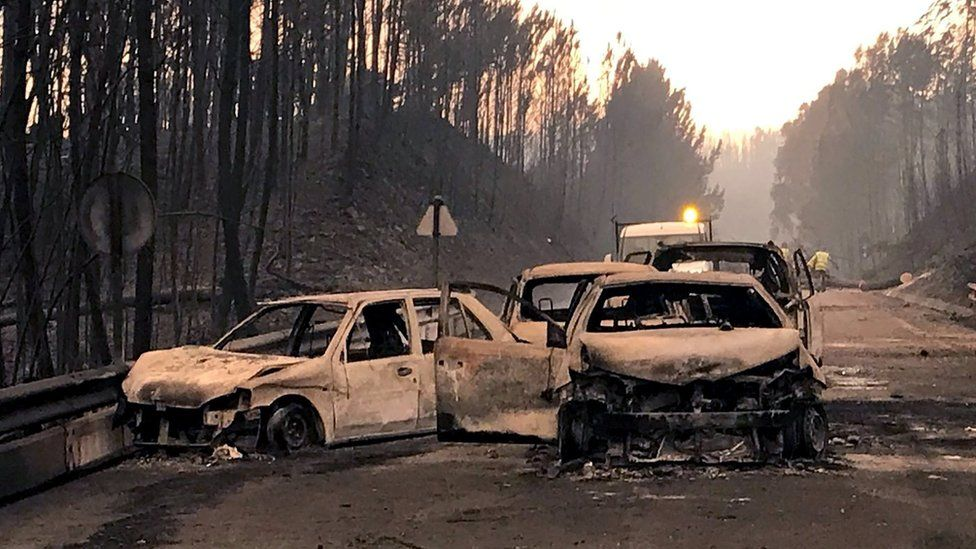 Burned cars are seen on a local road during a forest fire near Pedrogao Grande