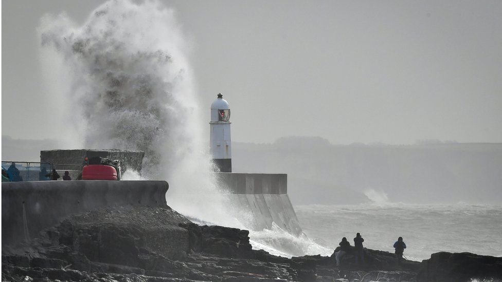 A wave slaps against the harbour wall at Porthcawl, Wales