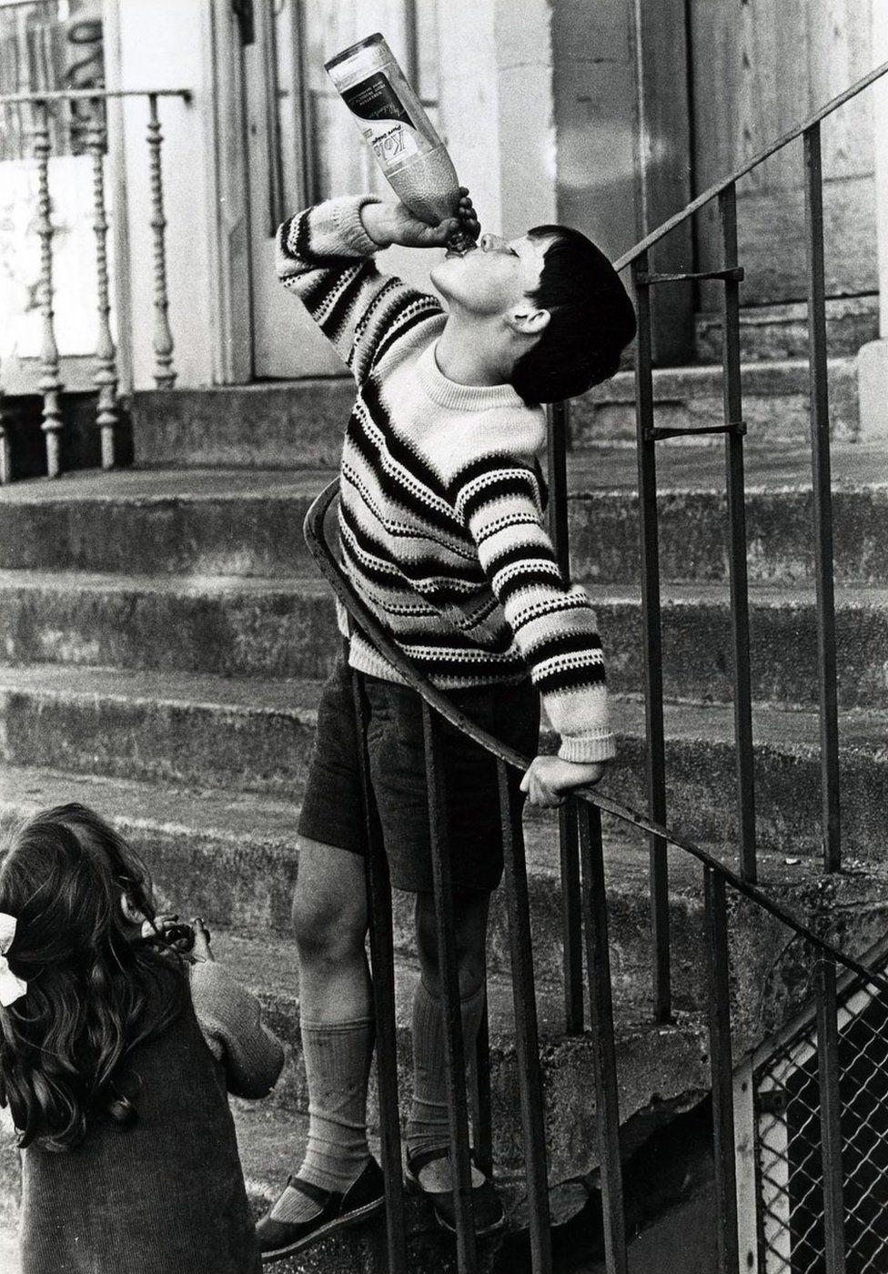 Boy swigging Coca-Cola, 1966