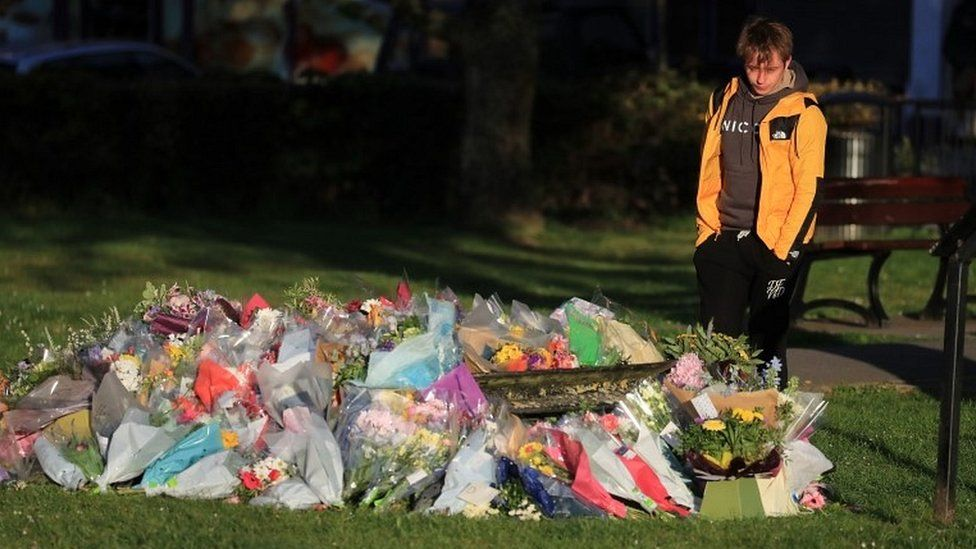 Patrick James, the son of PCSO Julia James, looks at floral tributes left near her family home in Snowdown