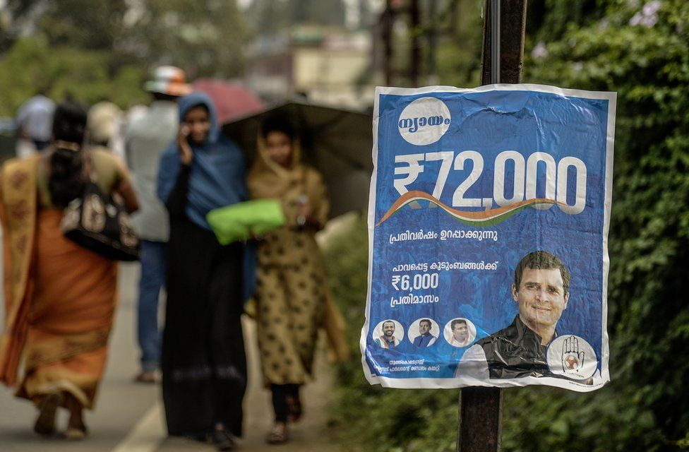 People walk past a poster of the Congress party's minimum income guarantee scheme for the poor