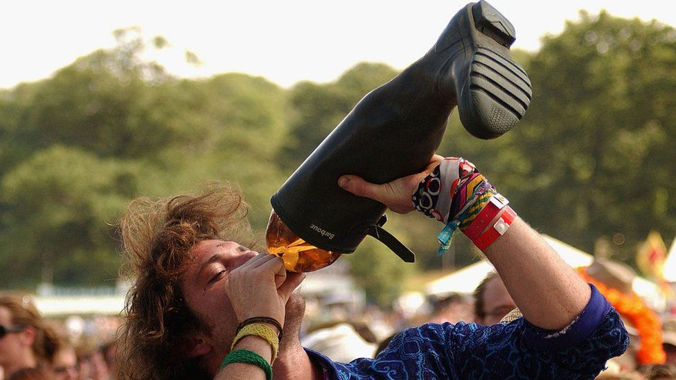 A man drinking from a welly