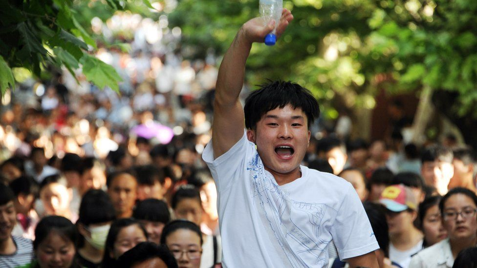 This picture taken on June 8, 2015 shows a high school reacting as they walk out of a school after sitting the 2015 national college entrance examination