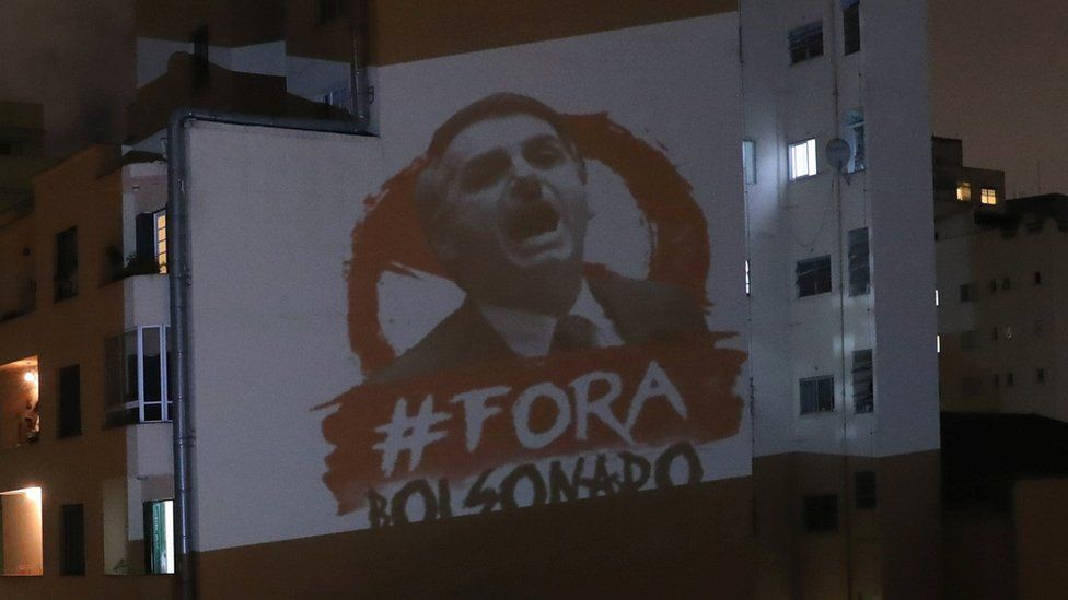 """An image depicting Brazil's President Jair Bolsonaro and the phrase """"Out Bolsonaro"""" projected onto a building in Sao Paulo (25 March 2020)"""