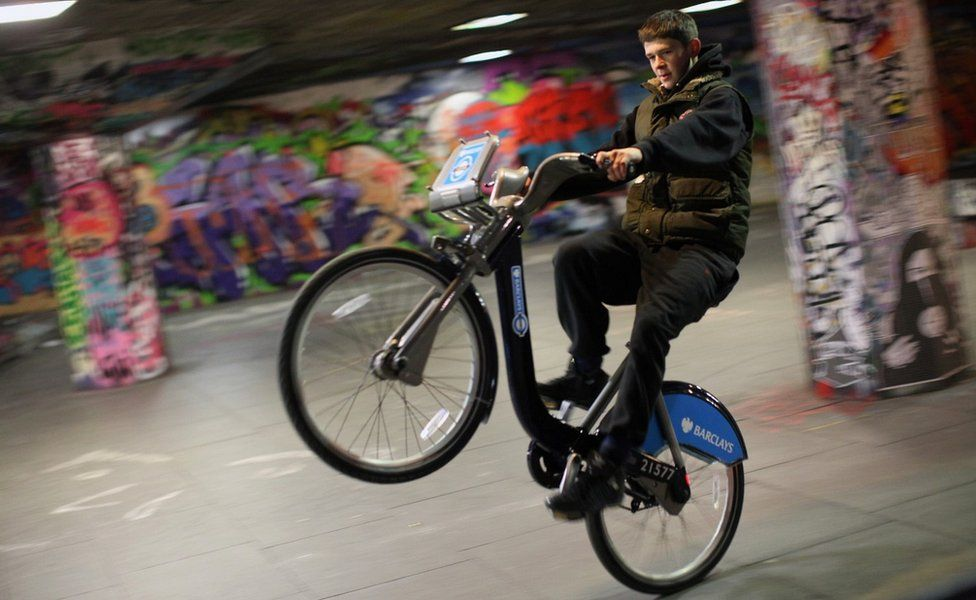 Teenager doing stunts on bike on South Bank