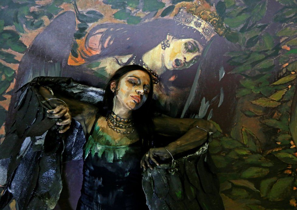 Model Alyona Alekseitseva presents a body of artwork by Russian artist Maria Gasanova, in Krasnoyarsk, Russia. Behind is a reproduction of Victor Vasnetsov's Sirin and Alkonost: A Song of Joy and Sorrow. 24 October, 2018