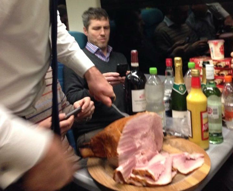 Commuters carving a ham on the train