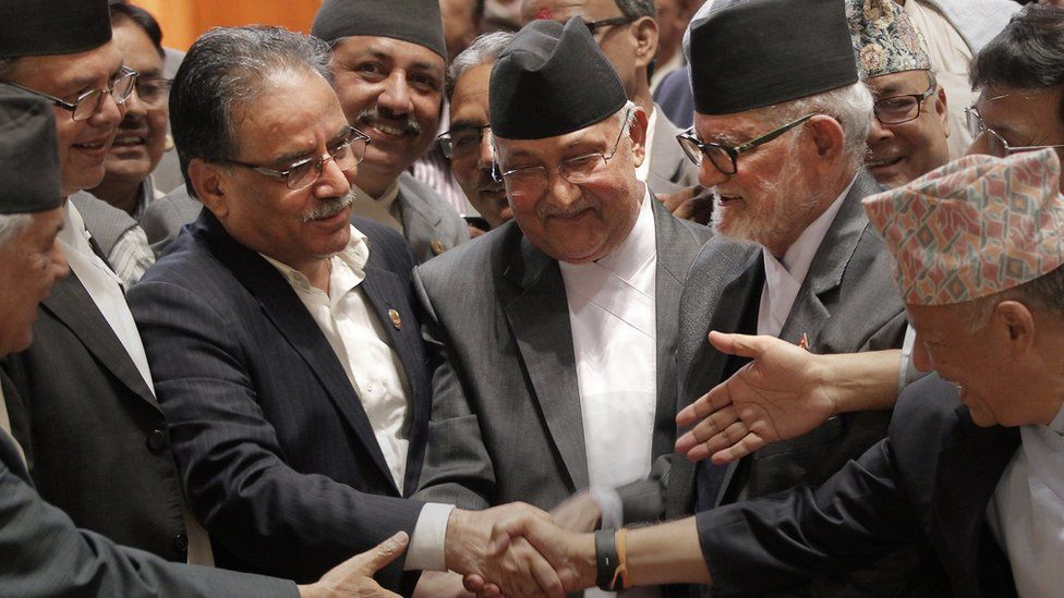 Nepal's Prime Minister Sushil Koirala, right, Communist Party of Nepal (Unified Marxist-Leninist), also known as CPN-UML leader K.P. Oli, center, and Communist Party of Nepal (Maoist) Chairman Pushpa Kamal Dahal, left, shake hands after the final constitution process at Constitution Assembly hall in Kathmandu, Nepal, Wednesday, Sept. 16, 2015