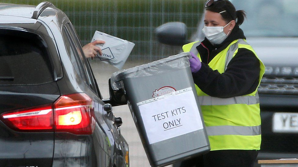 A motorist drops off a testing kit to a staff members wearing a protective face mask at an NHS coronavirus self-test site outside London's 02 arena