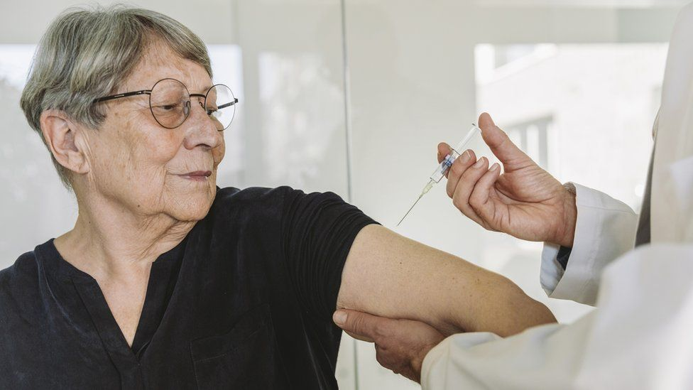 Doctor injecting vaccine into senior patient's arm