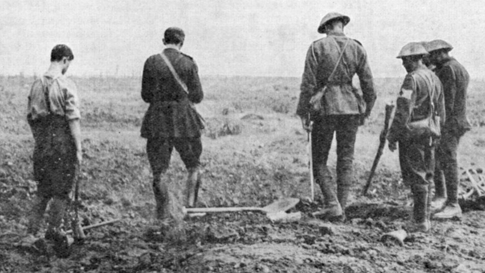 WWI Army chaplain conducting burial service in the field while a burial party stands by 1916