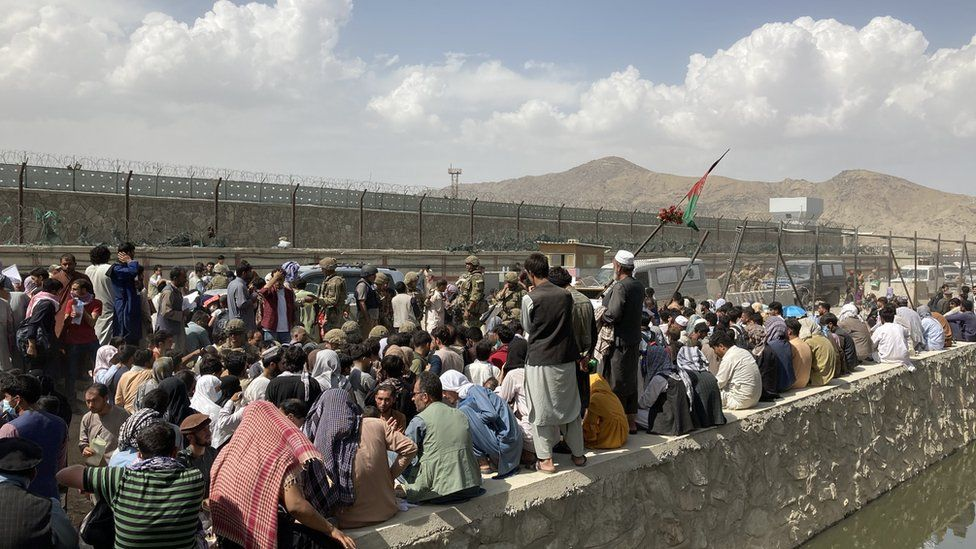 Afghans crowd outside the secure compound