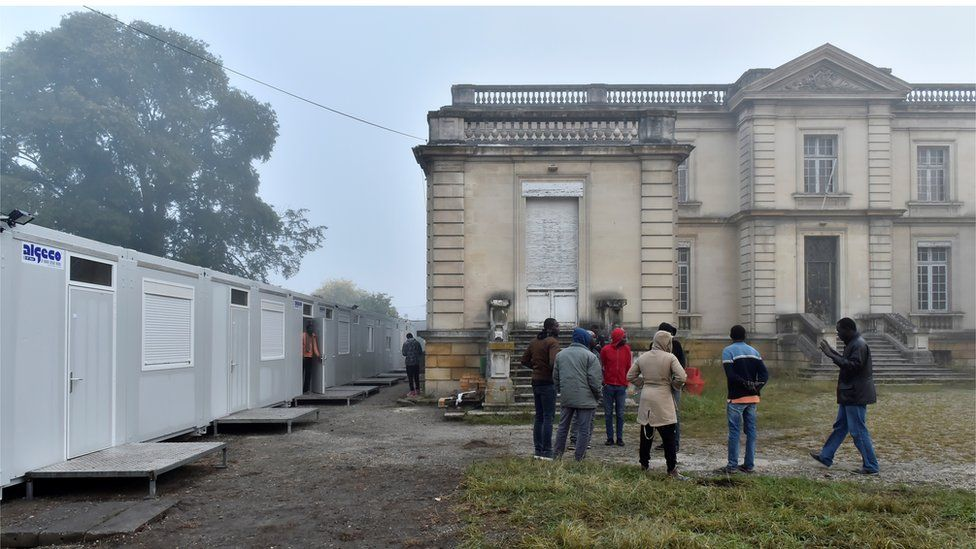 Sudanese migrants, who arrived overnight from the Calais ''Jungle'' camp, stand near temporary accommodations set up in front of the Chateau des Arts in Talence, one of the housing sites for migrants who left Calais, on October 25, 2016