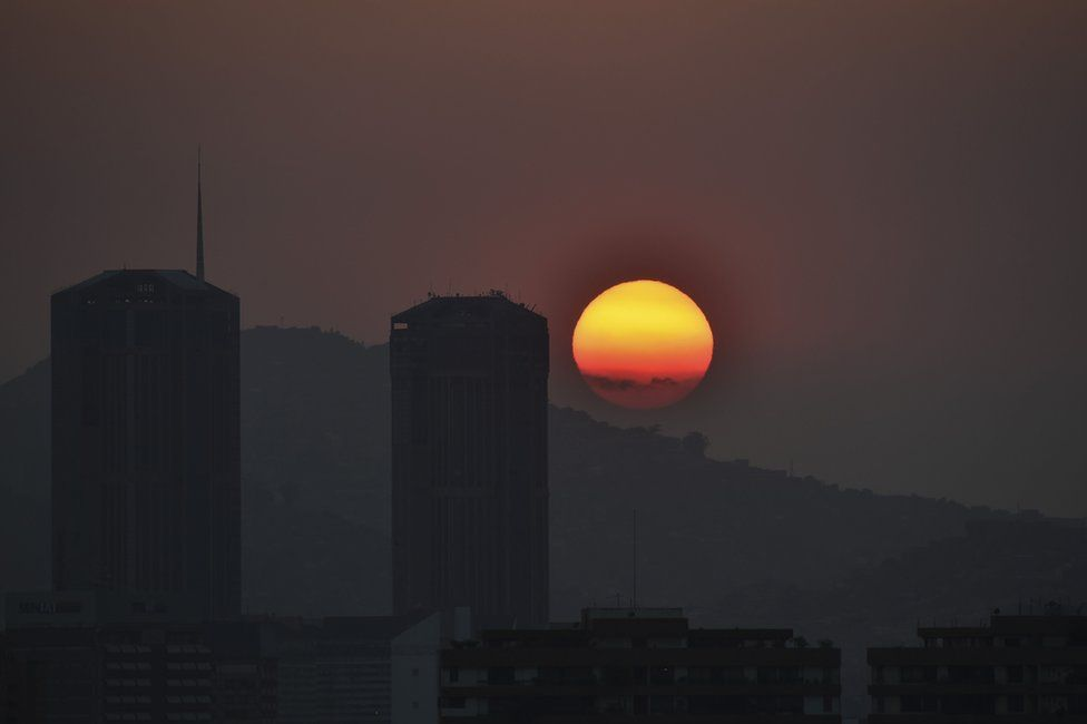 The sun sets in Caracas during a partial power cut on March 25, 2019.