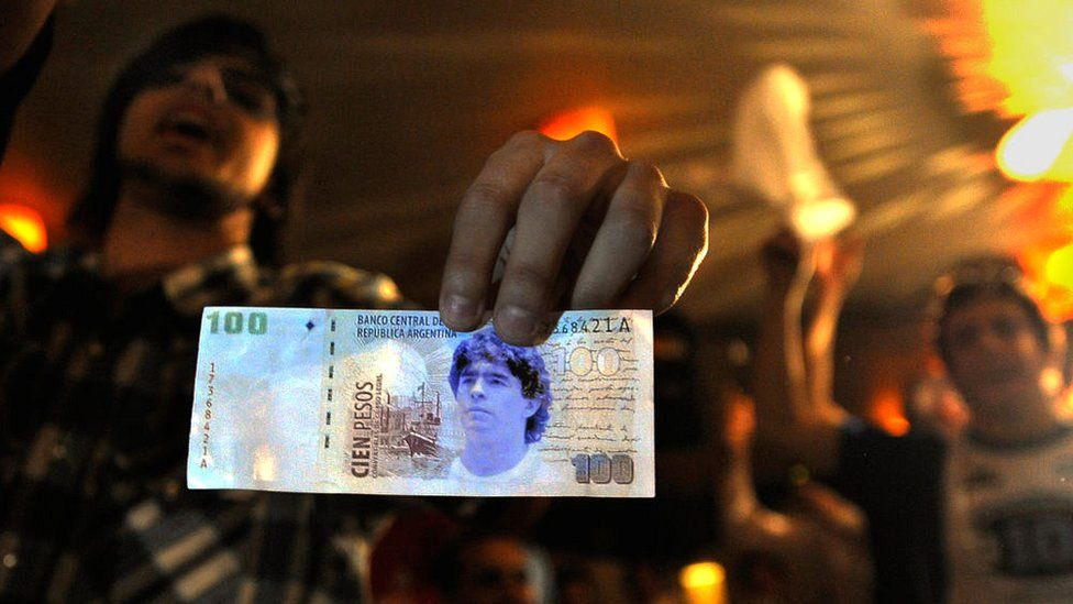 A member of the Maradonian Church The hand of God, a religion dedicated to the Argentina's greatest ever soccer player Diego Maradona, shows a fake one hundred pesos bill during their Christmas celebration in October 2008