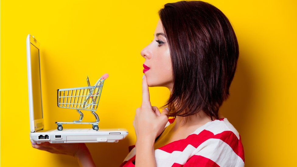 Woman with laptop and shopping trolley