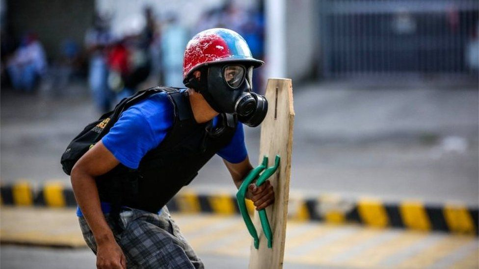 A protestor confronts members of the National Bolivarian Guard during a demonstration against the vote for a Constituent Assembly in Caracas, Venezuela, 30 July 201