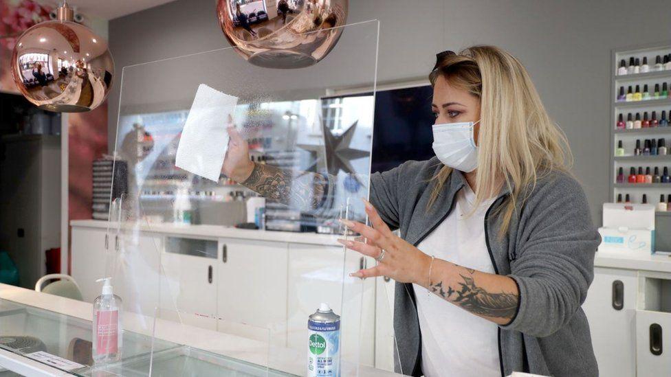 Shop owner wipes perspex screen