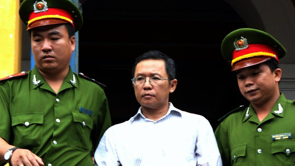 Pham Minh Hoang (C) being led out from the courtroom at the Ho Chi Minh City People's Court House on 10 August 2011.