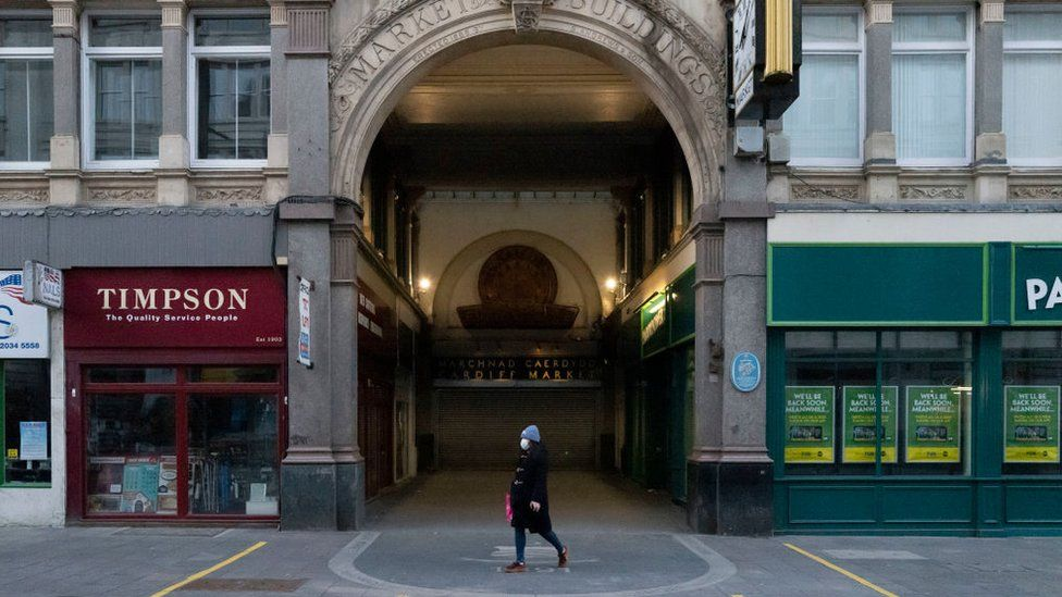 A lone woman walking past shut shops in Cardiff city centre