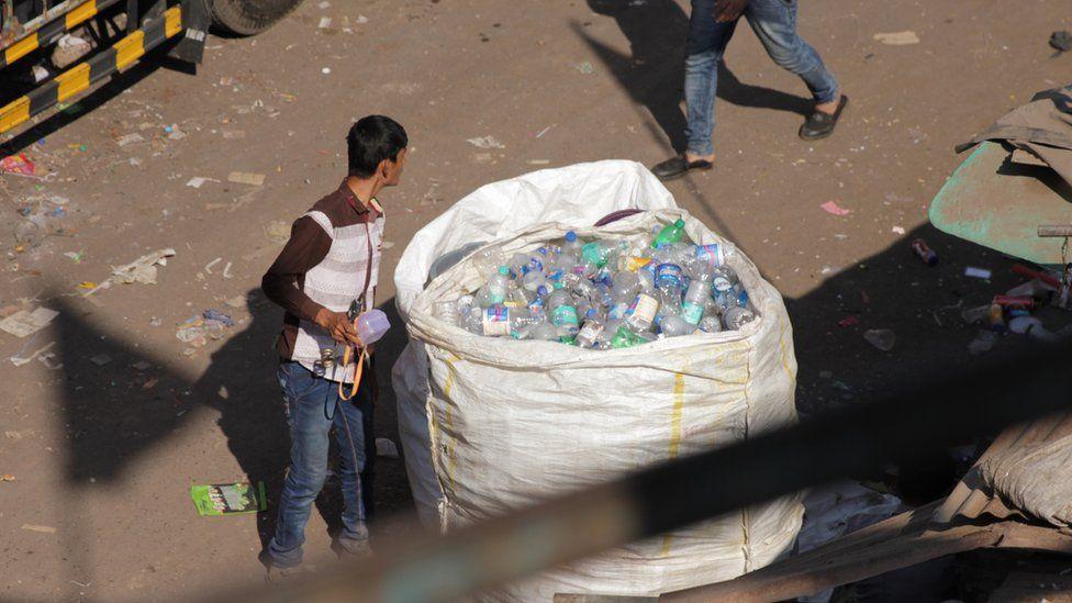 Man looking into bag of bottles in Dharavi