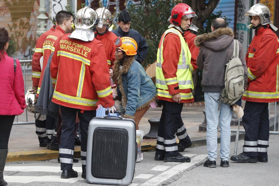 Firefighters and police evacuate people from the street where buildings collapsed in Marseille, 7 November