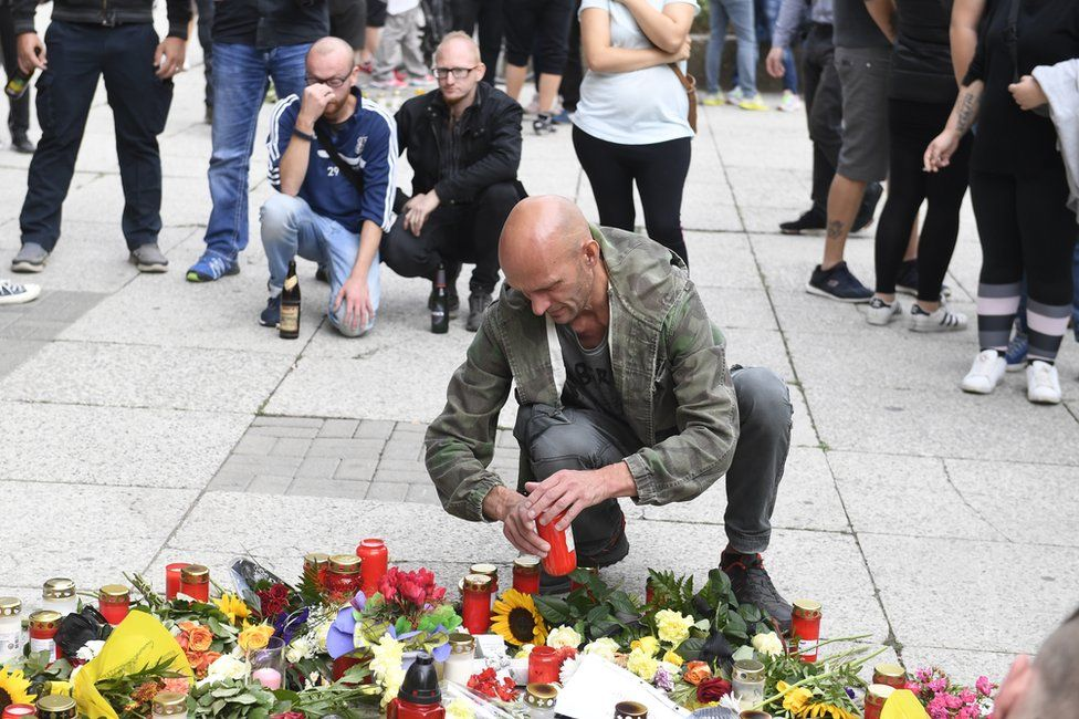 Candles and flowers mark the spot where the man was fatally wounded in Chemnitz