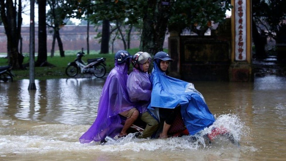 People ride a motorcycle along a flooded road after Typhoon Damrey hits Vietnam (04 November 2017)