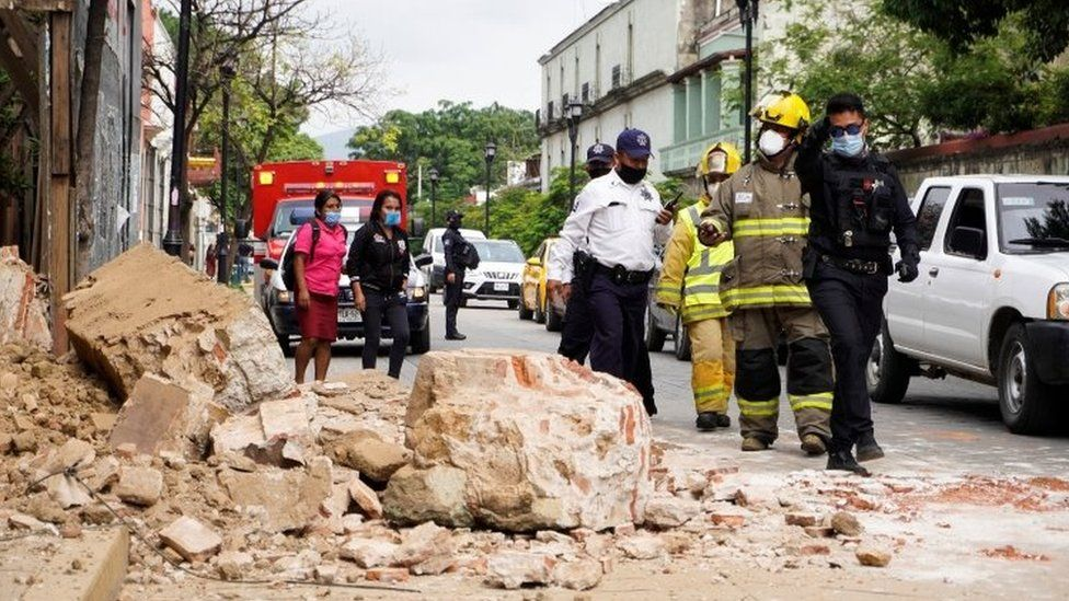 Members of the police and fire department observe the damage caused by a collapsed fence wall in Oaxaca, Mexico, 23 June 2020.