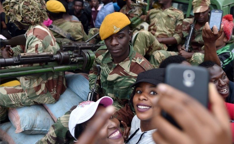 """A Zimbabwean Defence Force soldier poses for selfie-pictures with two women as they take part in a march in the streets of Harare, on November 18, 2017 to demand to the 93 year-old Zimbabwe""""s president to step down. Zimbabwe""""s president clings to office, the military is in power and the much-feared ZANU-PF party still rules - but Zimbabweans put such issues aside on November 18, 2017 to happily embrace what they hope is a new era for the country."""