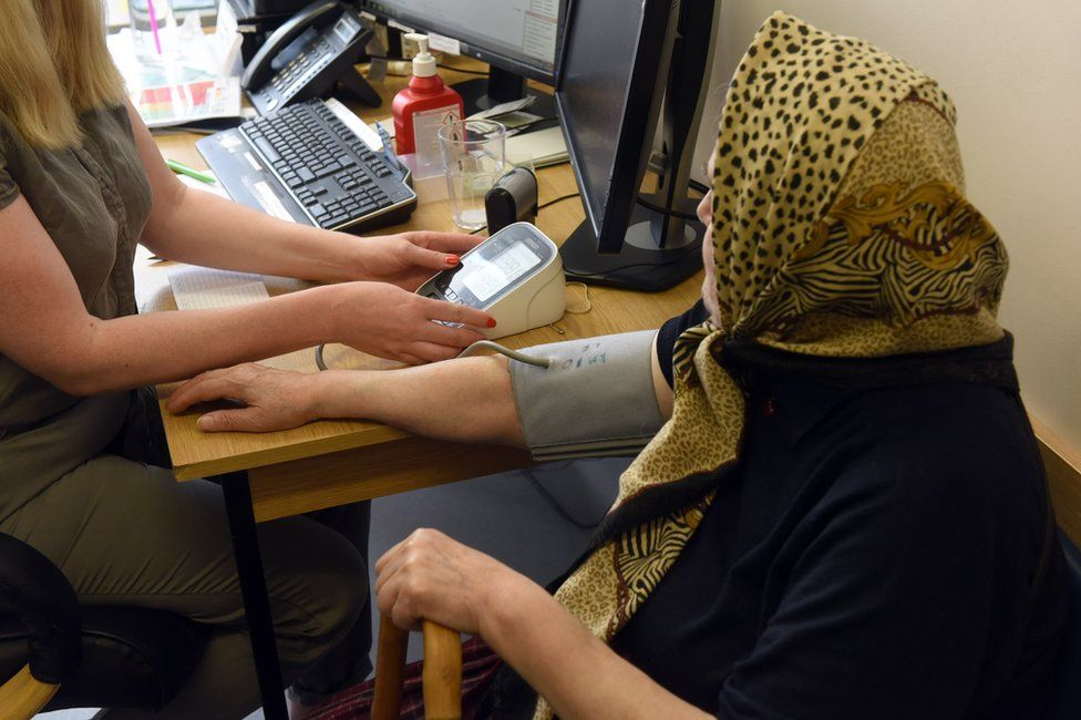 Doctor measuring old lady's blood pressure