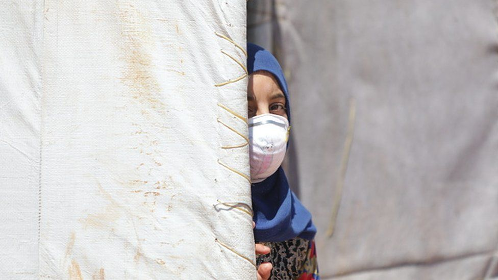 A Syrian girl wearing a medical mask as a precaution against coronavirus is seen at a refugee camp in Idlib