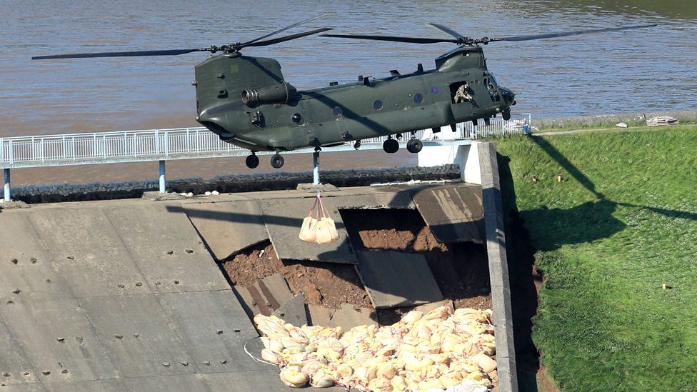 An RAF Chinook helicopter flies in sandbags to help shore a dam at Toddbrook reservoir