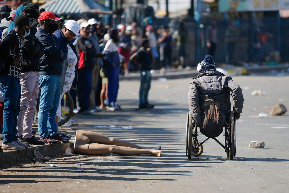 People look at a man in a wheelchair as he moves past the looted and vandalised Lotsoho Mall in Katlehong township, East of Johannesburg, on 12 July 2021
