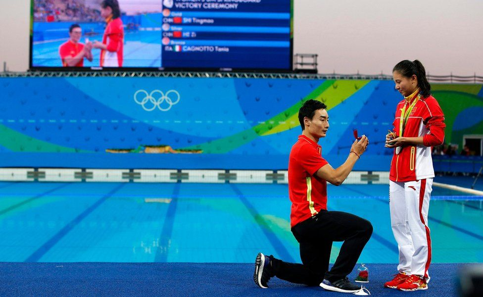 """He Zi (R) of China receives a marriage proposal from Chinese diver Ki Qin (L) after winning the silver medal in the women""""s 3m Springboard final of the Rio 2016 Olympic Games"""