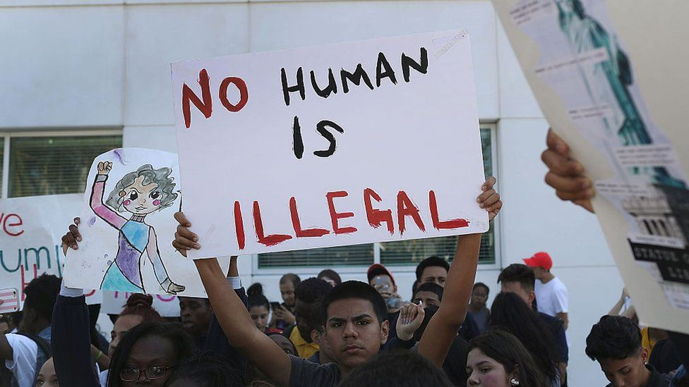 No Human is Illegal, a protesters sign reads