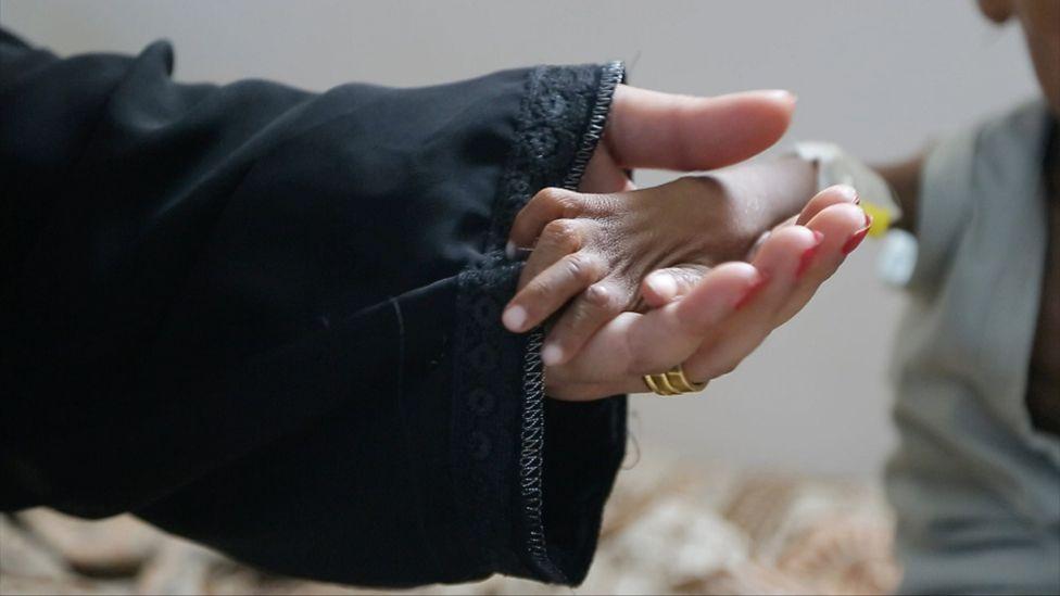 Ashaq holds hand of starving child