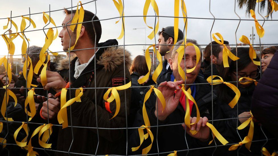 People tie yellow ribbons to a fence, as they protest in front of Germany's consulate after former president Carles Puigdemont