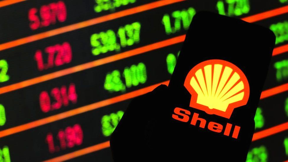 Shell logo on smartphone against stock market screen