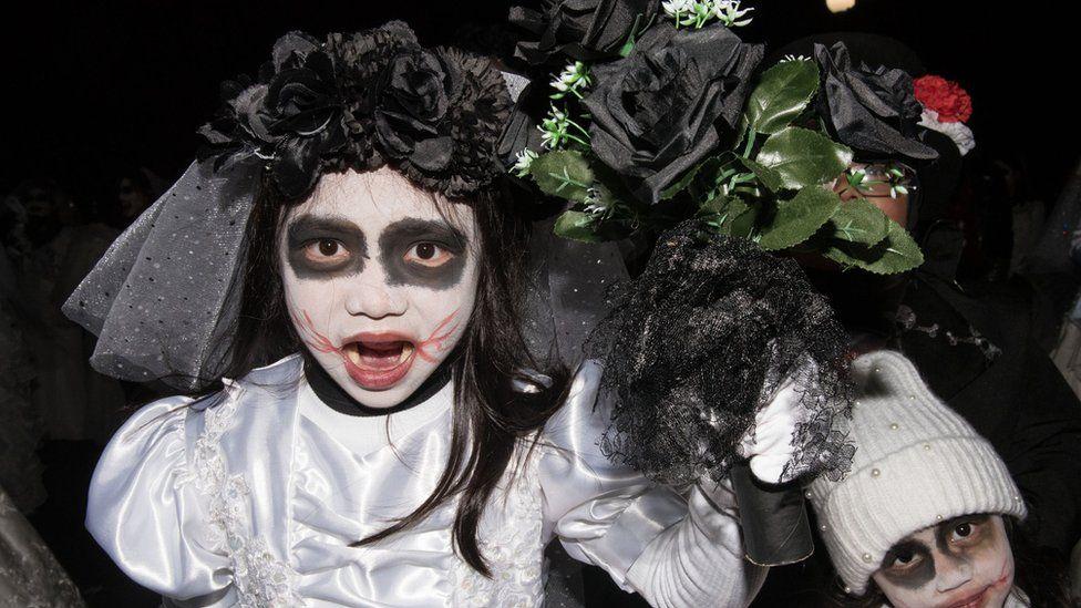 Children wearing zombie-bride costumes