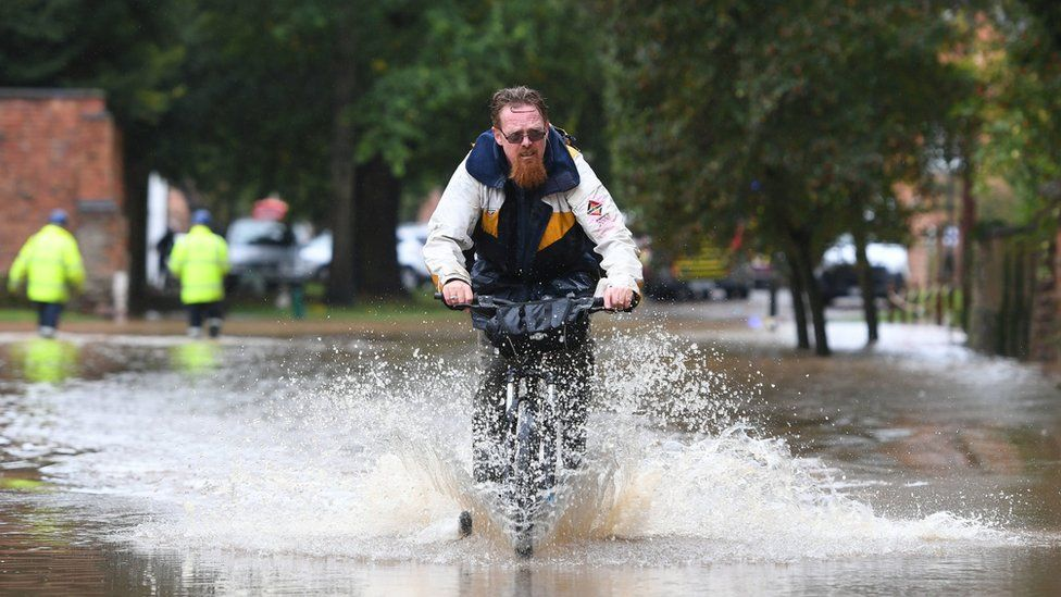 A cyclist riding through floods in Leicestershire
