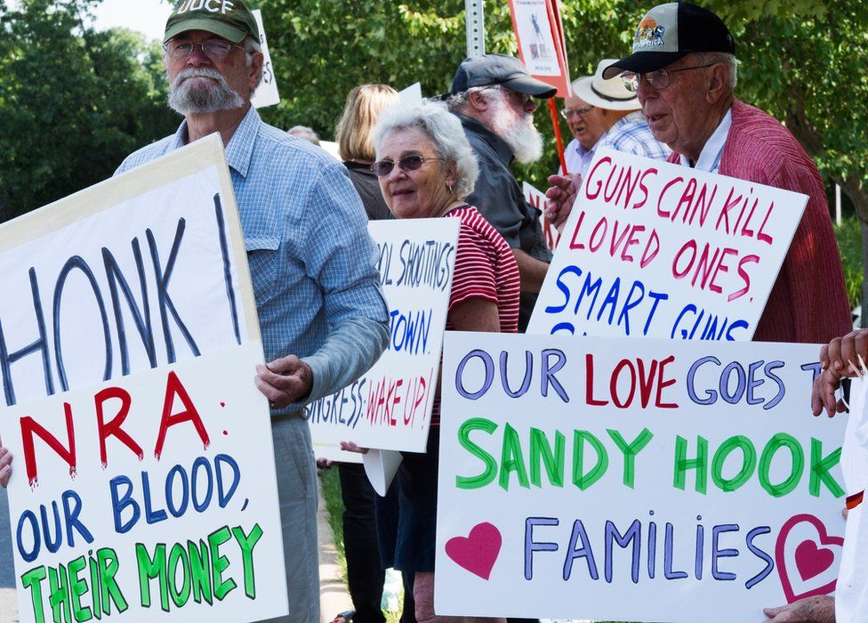embers of the Coalition of Gun Violence Prevention gather for their monthly protest outside the National Rifle Association(NRA) headquarters August 14, 2014, in Fairfax, Virginia.