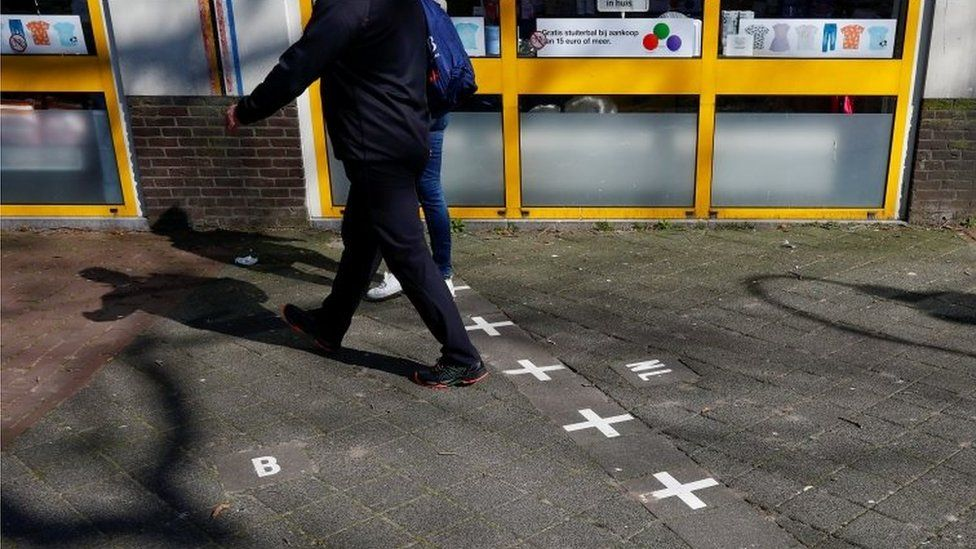 A couple crosses the border between Belgium and the Netherlands in Baarle on 26 March